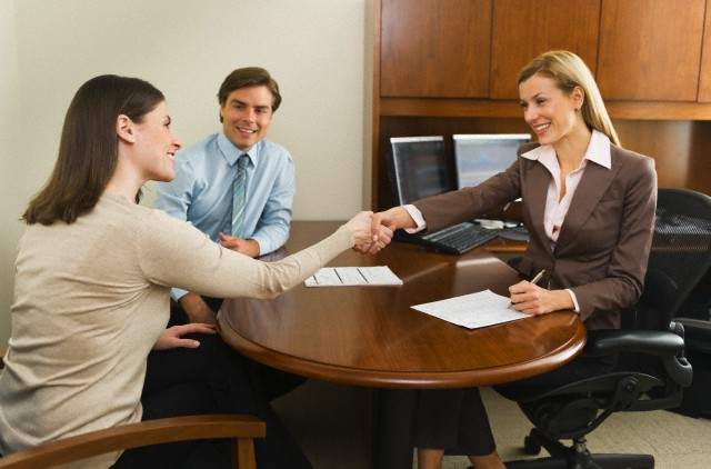 USA, New York, New York City, Businesswoman and clients shaking hands in office